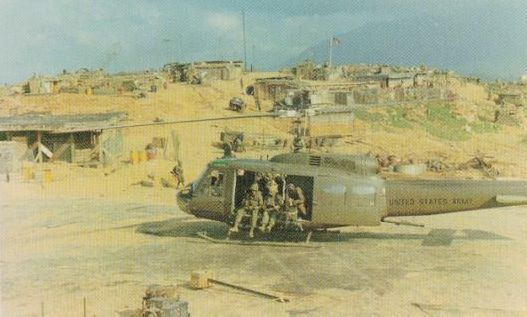 the mortar area looking generally from the north to the south. The VIP pad is in the background where the flag is visible. The tactical operations center (TOC) is in the center background with the tall antanna, to the left of the VIP pad. The ammo dump is at the right-front of the helicopter and the mess area is directly above the rotor hub. There is a wood latrine immediately between the top of the engine air intake cowling and the aft rotor. Note the bunkers at the extreme right of the photo
