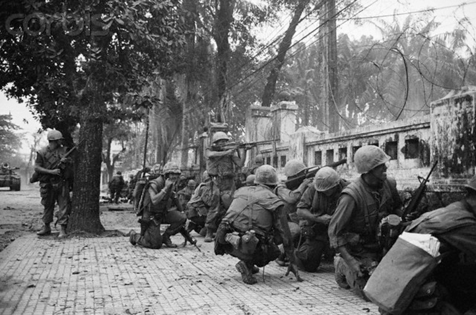 04 Feb 1968, Hue, South Vietnam --- 2/4/1968-Hue, South Viet Nam: U.S. Marines keeping lowbecause of intense sniper fire battle communist units which seized two thirds of the ancient imperial Capital. The Marines were pinned don behind this wall near the old citadel and radiod for support. U.S. spokesmen reported that leathernecks hauled down the North Vietnamese flag after seven days of fighting and recaptured the city. --- Image by © Bettmann/CORBIS
