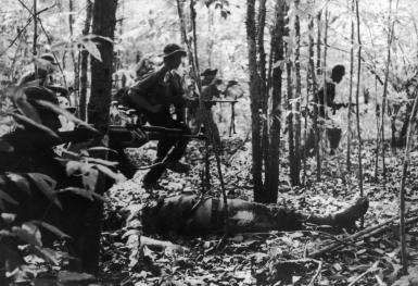 A Viet Cong detachment going into battle during the Vietnam War, January 1967. In the foreground is the body of a dead American soldier. (Photo by Keystone/Hulton Archive/Getty Images)