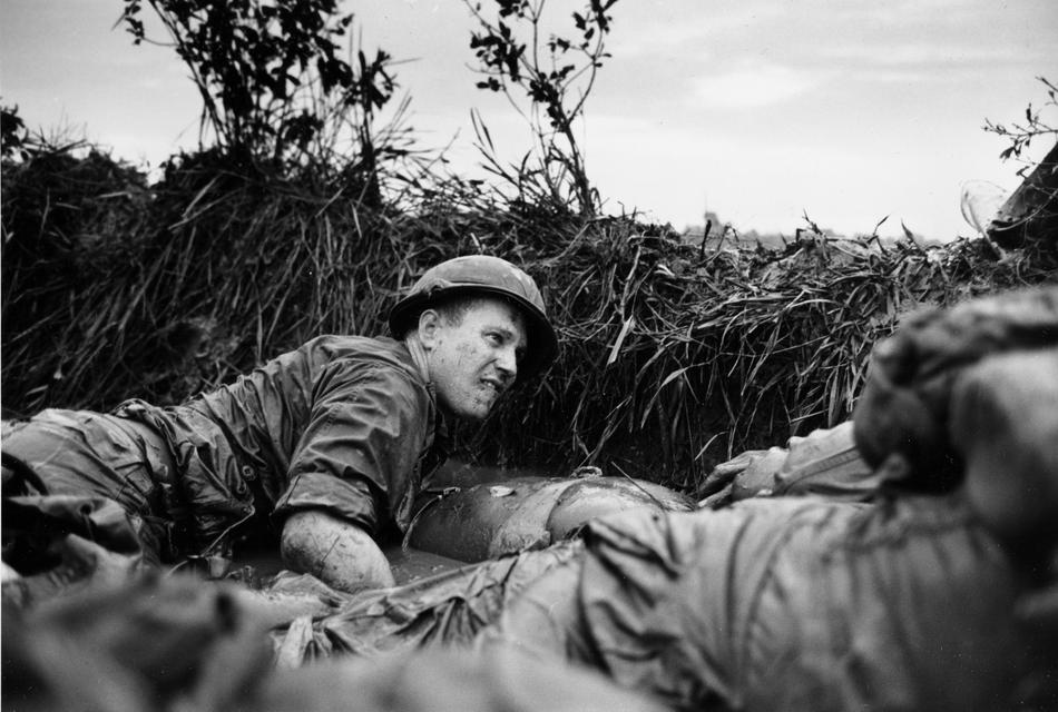 Pinned down by Viet Cong machine gun fire, a U.S. medic looks over at a seriuosly wounded comrade as they huddle behind a dike in a rice paddy, near Phu Loi, South Vietnam, August 14, 1966. (AP Photo)