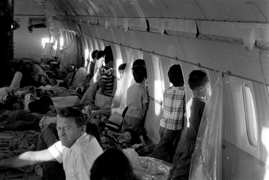 Orphans aboard the first babylift flight at the end of the Vietnam War crowd the windows of World Airways DC 8 jet as it flies them to the United States in April 1975. (AP Photo)