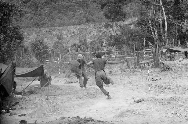 U.S. Marines run to their foxholes as North Vietnamese mortars begin zeroing in on their positions during Operation Hastings near the demilitarized zone between North and South Vietnam on July 17, 1966. (AP Photo/Horst Faas)