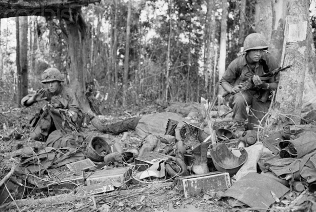 22 Nov 1967, Dak To, South Vietnam --- In Battle. A member of the 173rd Airborne Brigade crouches beside the body of a dead comrade and equipment left by wounded at the height of the battle on Hill 875. U.S. Army paratroopers of the 173rd Airborne Brigade began a final assault up the bloody slopes of Hill 875.