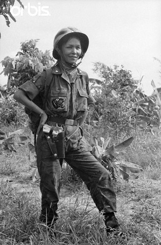 """19 Jun 1965, South Vietnam --- A pearl-handled .45 automatic on her hip, HoThi Que - """"Tiger Lady"""" of the vital MeKong Delta in Suth Viet Nam watches the 44th Vietnamese Ranger Battalion march into the jungle in pursuit of Red Viet Cong Guerrillas. The Battalion - Recently awarded the US Presidential Citation for Extraordinary Hero- is under the command of Major de Van Dan, who is her husband. --- Image by © Bettmann/CORBIS"""
