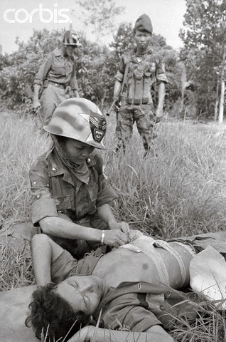 """19 Jun 1965 --- When the """"Tiger Lady"""" isn't actually fighting alongside her husband and his Rangers, she helps to care for the wounded in the field. Her presence in the combat zone has contributed importantly to the high morale of the 44th South Vietnamese Ranger Battalion. The unit's Tiger head insignia appears on her helmet. --- Image by © Bettmann/CORBIS"""