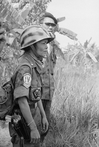 19 Jun 1965 --- serves as a combat master sergeant under the command of her husband, Major Le Van Dan (rear, with glasses), in the crack 44th South Vietnamese Ranger Battalion. The unit has never lost a battle or a gun- to the Red Viet Cong Guerrillas. The major and his fighting wife have seven children. --- Image by © Bettmann/CORBIS
