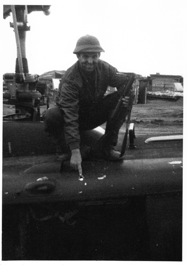 The author pointing to one of the bullet holes from the mission noted in this article, while wearing a captured NVA pith helmet and holding his M-79 grenade launcher at LZ Hawk Hill in early January 1970. (Photo courtesy of the author.)